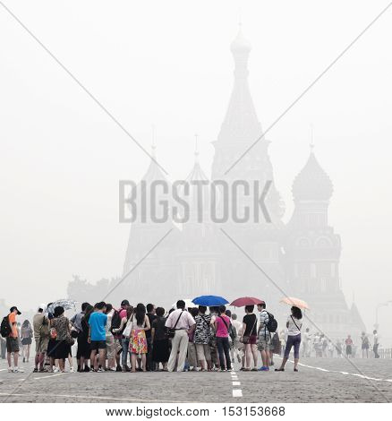 MOSCOW - AUGUST 7, 2010: A group of tourists on the Red Square under smog on august 6, 2010 in Moscow. City covered smoke from burning forests.
