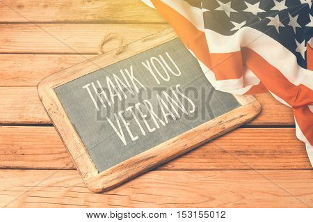 Veterans day background with chalkboard on wooden table and USA flag poster