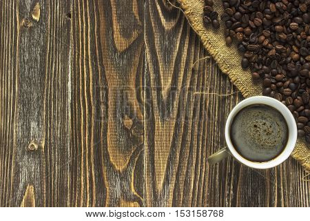 A cup of coffee and crema is in the corner of a wooden table on a burlap canvas close to crumble coffee beans. Close up. Top view