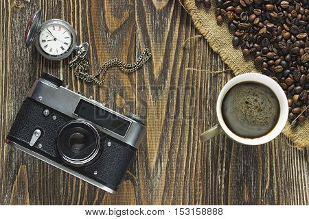 Obsolete vintage camera a silver pocket watch and a mug of coffee with crema and the coffee beans standing on a burlap canvas on a wooden background. Colose up. Top view