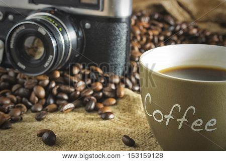 Outdated vintage camera and a mug of coffee with crema and the coffee beans standing on a burlap canvas on a wooden background. Close up