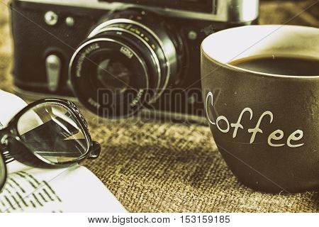 Old textbook with glasses lying near the outdated camera and a cup of coffee with crema and coffee beans on burlap canvas on a wooden table. Close up. Retro styled