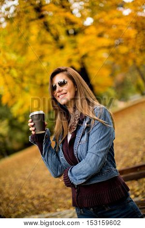 Young woman with coffee to go in the autumn park