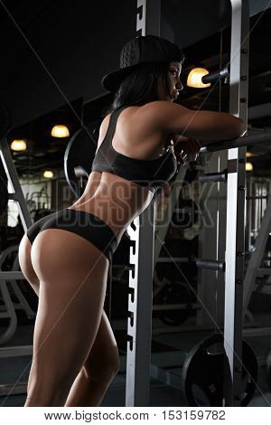 Back view of brunette sexy fitness girl in sport wear with perfect body in the gym posing.