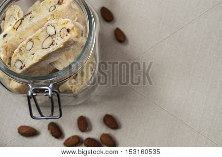 close up of tub of biscotties standing on cloth with lying almonds