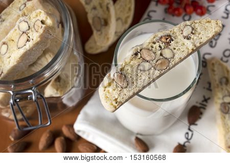 close up of tub of biscotties and glass of milk standing on table with lying almonds