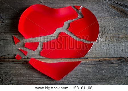 Broken heart red plate concept on wooden board