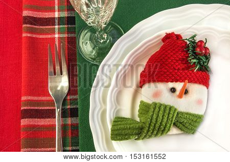Holiday table setting with two white plates fork wineglass snowman and Christmas decorations over colorful napkins. Top view. Horizontal.