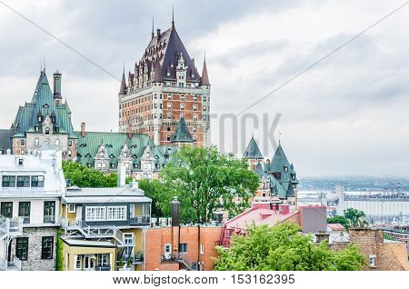 Quebec City, Canada - July 27, 2014: View of old town houses on hill with Fairmont Le Château Frontenac in downtown and Saint Lawrence river