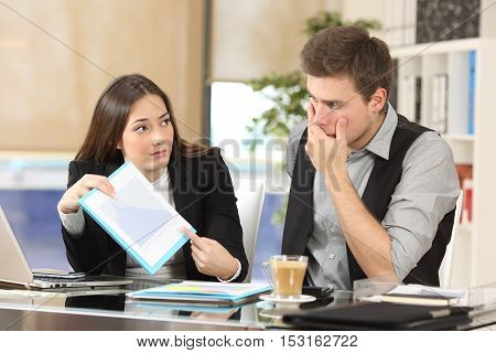 Worried coworker showing a growth graph with bad results to her partner at office