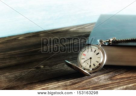 Old vintage silver pocket watch and book with black cover on wooden table. Blurred. Soft focus