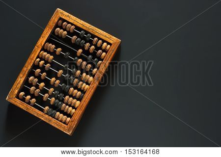 Old wooden scratched vintage decimal abacus on a black desktop from chalkboard with blank for inscription for the background. Top view. Flat lay.