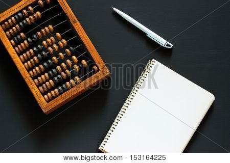 Old wooden scratched vintage decimal abacus pen and empty notepad on a black desktop from chalkboard with blank for inscription for the background. Top view. Flat lay. Mock up