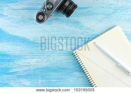 blank notebook with a ballpoint pen and old vintage photo camera on blue wooden background. Mock up. Top view. Flat lay.