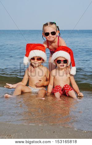 children in Christmas hats and sunglasses frolic in the sea