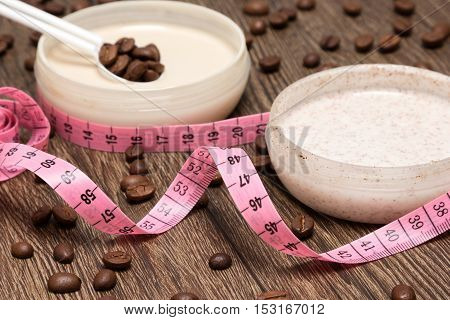 Weight loss and cellulite busting concept. Body measuring tape and anti-cellulite cosmetic products with caffeine. Shallow depth of field