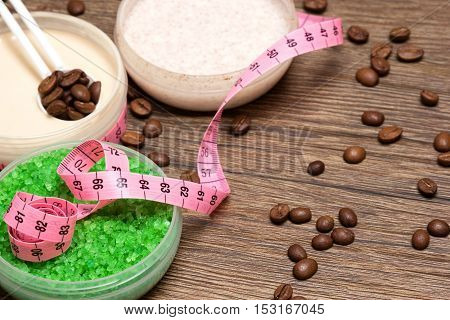 Anti-cellulite cosmetic products with caffeine and body measuring tape on wooden surface. Shallow depth of field, copy space