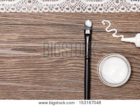 Beauty products for skin around the eyes. Eye cream squeezed out of tube, glass jar of light gel for eyelids and applying brush with sample on wooden surface with white lace tape. Copy space
