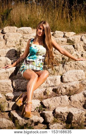 Caucasian long hair model in dress sitting on rocks.