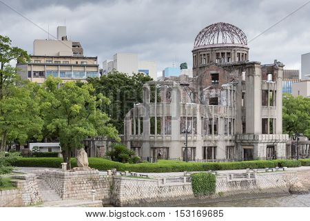 Hiroshima Japan - September 20 2016: Ruin of Hiroshima Prefectural Industrial Promotion Hall has become the A-Bomb Memorial in Hiroshima. One of the few buildings with some walls left erect. River in front cloudy sky other buldings