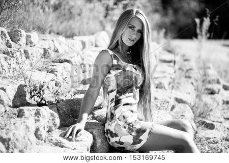 Caucasian long hair model in dress sitting on rocks. Black and white picture.