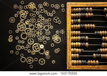 Old wooden scratched vintage decimal abacus and steampunk gears on a black desktop from chalkboard with blank for inscription for the background. Top view. Flat lay.
