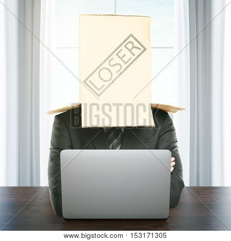 Cardboard box with 'loser' stamp on the head of a businessman using laptop at workplace. Failure concept. 3D Rendering