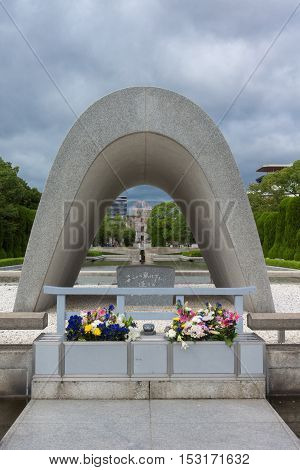 Hiroshima Japan - September 20 2016: The Memorial Cenotaph with the A-bomb ruin memorial at the far end it the Peace Memorial Park looking over the pool and eternal flame. Flowers and cloudy sky.