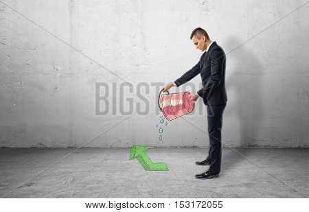 A businessman full-height in profile holding a red bucket with water pouring out of it on a green arrow pointing up, all on the background of a grey wall. Business and investment. Successful people. Getting profit.