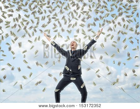 A happy businessman in a celebrating pose with loads of money in the air, all on the background of the sky. Business and finance. Succesful people. Earning money.