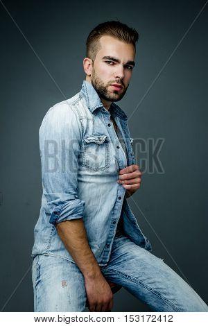 Handsome bearded man wearing jeans shirt, portrait shot in studio