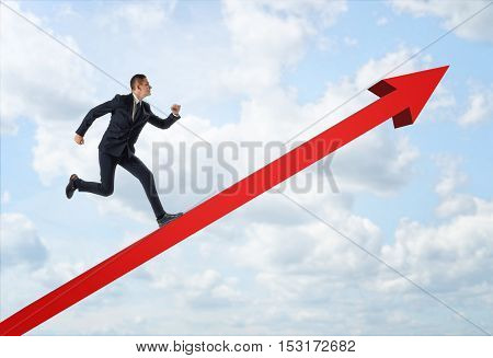 Businessman running up the big red arrow on the background of the blue sky. Business and management. Way to success. Reaching aims.