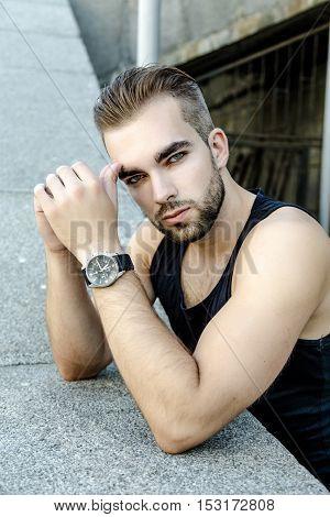 Handsome bearded man wearing sleeveless shirt, portrait shot in urban area