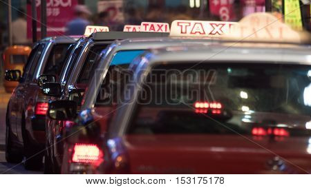 Queue of taxi cars in night street. Cabs with illuminated signs on the roofs parked in a row waiting for clients