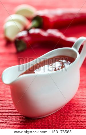 Bowl of thai sweet chili sauce on the red background