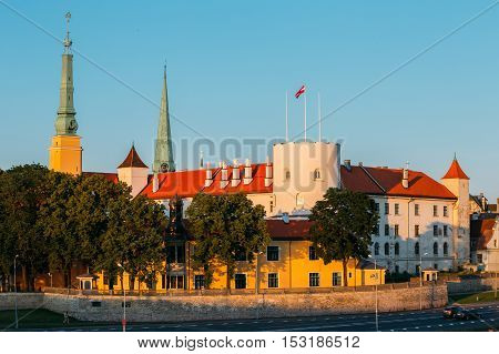 Latvia. Riga Castle, The Famous Historical Cultural Medieval Landmark Of Late Classicism And Official President Residence On The Bank Of Daugava River In Sunny Summer Day With Blue Clear Sky.