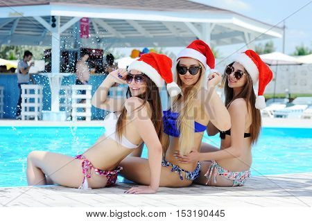 Three friends in bathing suits and caps of Santa Claus on a background of the pool. Christmas holidays in warmer climes.