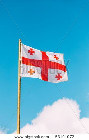 Close The Flag Of Georgia, Five Cross Flag, Waving On Flagpole At Blue Sunny Sky Background. The White And Red National Symbol, Civil And State Ensign Of Georgia.