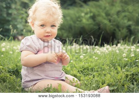 Shy baby girl on grass among blossoming flowers in summer park in sunny day with copy space