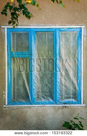 Blue window of the building under the polyethylene film