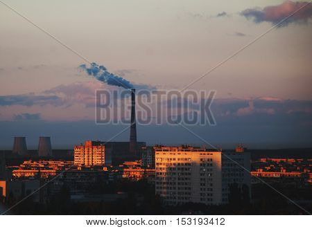 Urban landscape at sunset. Smoke from the chimney of CHP