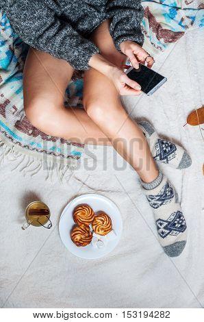 Long female feet in warm woolen socks with smartphone.