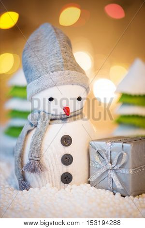 Cute festive snowman with Christmas present Christmas lights in background