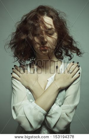 Portrait of girl meditating with closed eyes over gray background