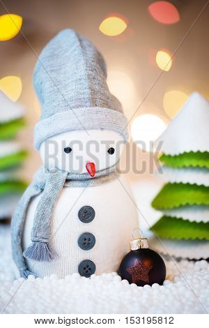 Cute festive snowman in a forest with Christmas ball Christmas lights in background