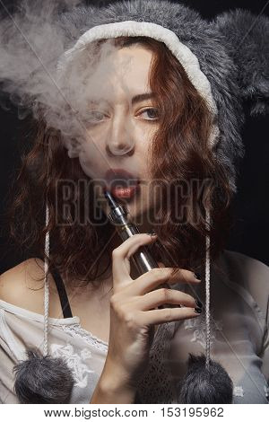 Sexy girl with electronic cigarette in funny bear hat