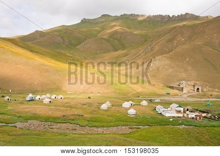 Mountain meadow with the asian yurts and ancient fort Tash Rabat, Kyrgyzstan. Kyrgyzstan's population is 5.2 million. The country is rural