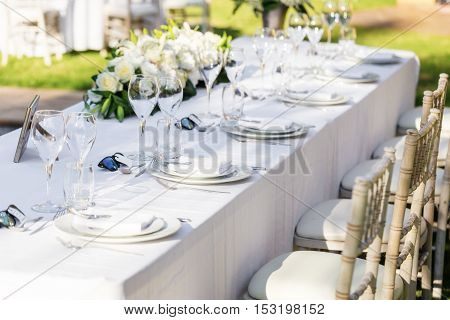 Wedding table decorations. Close-up. Flowers plates utensils