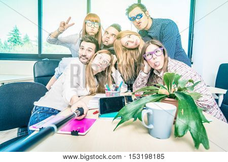Group of happy students employee workers taking selfie with stick - University business concept of human resource on working fun time - Start up entrepreneurs at college office - Bright lomo filter