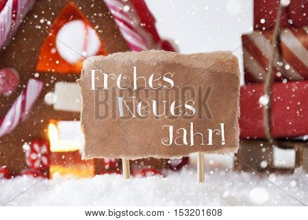 Gingerbread House In Snowy Scenery As Christmas Decoration. Sleigh With Christmas Gifts Or Presents And Snowflakes. Label With German Text Frohes Neues Jahr Means Happy New Year